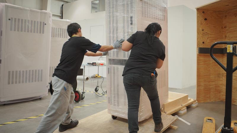 Employees moving properly packed equipment into a crate